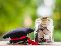 Saving money for education concept. Coins in glass jar with grad. Uate hat on blur background Royalty Free Stock Photos