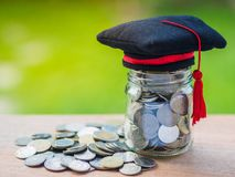 Saving money for education concept. Coins in glass jar with grad. Uate hat on blur background Royalty Free Stock Photo