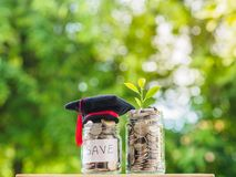 Saving money for education concept. Coins in glass jar with grad. Uate hat on blur background Stock Images