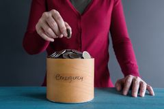 Saving Money for Emergency Concept. Woman putting Coin into a Bo. X Stock Images