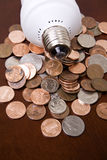 Saving money on energy. Using energy efficient lighting to save money concept with American money change on a table with a flourescent light on top royalty free stock photos
