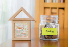 Saving money with family home word cloud. Saving label on money jar and wooden home blocks with house and family word cloud stock photography
