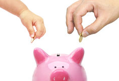 Saving money. Father and a baby do saving money in a pink piggy bank Royalty Free Stock Photography