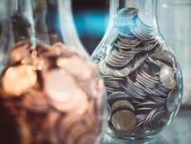 Saving Money Finance concept Coin collect Coinbank. Blur Glass bottle Stock Photos