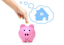 Saving money for future. Hand putting a coin into a pink piggy bank thinking of buying a new house - saving money for future concept Stock Photos