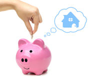 Saving money for future. Hand putting a coin into a pink piggy bank thinking of buying a new house - saving money for future concept Stock Photo