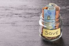 Saving money in a glass jar stock photography