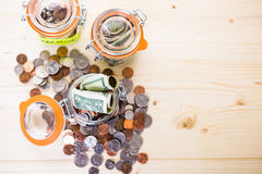 Saving money. Into glass jar for future investment Royalty Free Stock Image