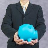 Saving money, hand putting coin into piggy bank Stock Photos