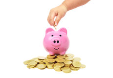 Saving money. Hand of a young baby giving golden coin to a piggy bank sitting on pile of golden coins Stock Photography