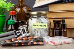 Saving money for health care insurance - money glass, stethoscope, pills and bottles royalty free stock images