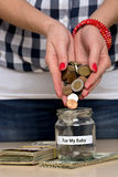 Saving money for her baby. Young woman pouring coins into a jar. She is saving money for her baby Stock Images