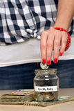 Saving money for her baby. Young woman putting coin into a jar. She is saving money for her baby Stock Images