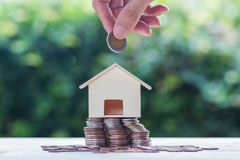 Saving money, home loan, mortgage, a property investment for fut. Ure concept : A man hand putting coins over small residence house on stack coins with green royalty free stock images