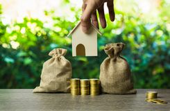 Saving money, home loan, mortgage, a property investment for future concept. A man hand holding house model over stack of coins. And money bag with nature royalty free stock image