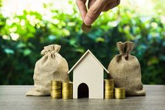 Saving money, home loan, mortgage, a property investment for future concept. A man hand putting money coin over small residence. House and money bag with nature stock images