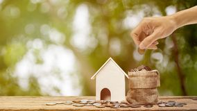 Saving money, home loan, mortgage, a property investment for future concept. A man hand putting money coin over money bag and small residence house with nature stock photo