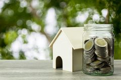 Saving money, home loan, mortgage, a property investment for future concept. A small residence house and money coins in jar on wood table and space with green royalty free stock photography