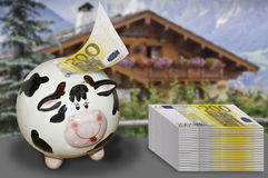 Saving money for a house. This image shows a pile of banknotes and a piggy bank in introducing a bank note. The background is a house of focus. Symbolizes saving Royalty Free Stock Image