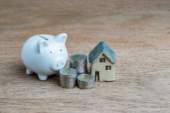 Saving money for house concept with white piggy bank, coins stac stock images