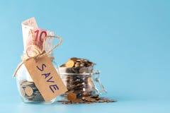 Saving money in jar Royalty Free Stock Images