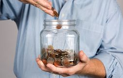 Saving Money In Jar. Man drops money into a glass jar for a savings account Stock Images