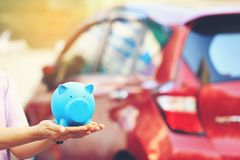 Saving money and loans for car concept, Young woman holding blue piggy bank with standing at the car parking lot background, Auto royalty free stock photos
