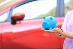 Saving money and loans for car concept, Young woman holding blue piggy with standing at the car parking lot background, Auto stock image