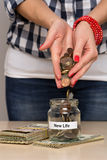 Saving money for new life. Young woman pouring coins into a jar. She is saving money to start a new life Stock Image