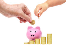 Saving money. Old hand of the elderly and a baby hand putting golden coins into a pink piggy bank concept Royalty Free Stock Photos