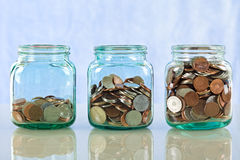 Saving money in old jars. Saving money concept - coins in old jars on reflective surface against blue background royalty free stock photos