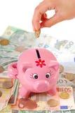 Saving money in piggy bank Royalty Free Stock Photography