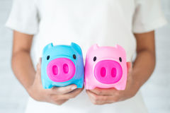 Saving money in a piggy bank. Saving money for the future in a piggy bank Royalty Free Stock Images