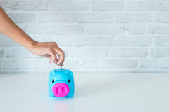 Saving money in a piggy bank. Saving money for the future in a piggy bank Royalty Free Stock Photo