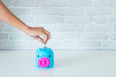 Saving money in a piggy bank. Saving money for the future in a piggy bank Royalty Free Stock Photography