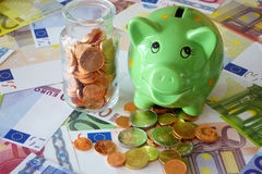 Saving money in a piggy bank. Small glass bottle with Euro coins and a green piggy bank on background made of euro banknotes and coins Stock Photos