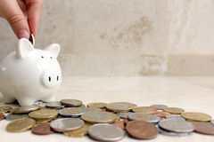 Saving money in a piggy Royalty Free Stock Photos