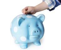Saving money in a piggybank. A child's hands placing coin money into a blue piggybank stock photos