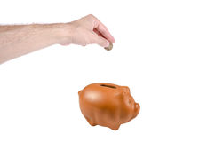 Saving money. In a piggybank - isolated over a white background Stock Photo