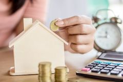 Saving money and planing to buy home concept with blur background of woman hand putting coin in house model Royalty Free Stock Image