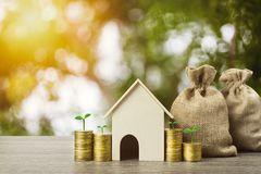 Saving money or property investment or buy a new home concept. A small house model with growth plant on stack of coins and money. Bag on wood table. Depicts stock images