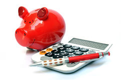 Saving money. Red piggy bank with calculator and ball pen Royalty Free Stock Photos
