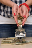 Saving money for retirement. Young woman pouring coins into a jar. She is saving money for retirement Stock Photos