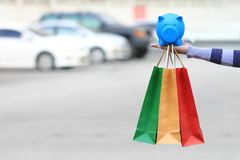 Saving money for shopping and for car concept, young woman holding blue piggy and shopping bags on the car parking lot background stock images