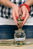 Saving money for summer holiday. Young woman pouring coins into a jar. She is saving money for summer holiday Stock Photography