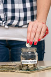 Saving money for summer holiday. Young woman putting coin into a jar. She is saving money for summer holiday Royalty Free Stock Photo