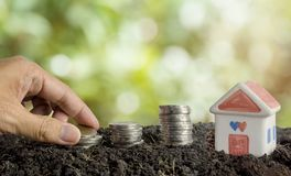 Saving money to build a house concept, house and coins in soil royalty free stock photography