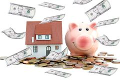 Saving money to buy a house or a property concept with piggy bank and pile of coins and banknotes Stock Photo