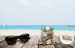 Saving money for vacation concept, glass coins container with sunglasses on wooden table at tropical beach Stock Photography
