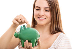 Saving money. Young girl putting money in a piggy bank isolated on white background Stock Images